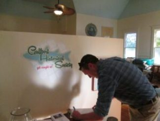 Jon Kile signs the visitors book at the Gulfport History Museum.