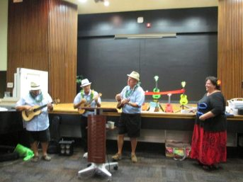 """Tampa Bay Ukulele Society members performed a lively rendition of """"Strumming My Cares Away,""""  then Cheryl Morales, executive director of the Pinellas Public Library Cooperative, cut the ribbon and thanked everyone who made the Ukulele Lending Library program possible in Hawaiian."""