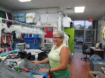 Jan Ritz, Clothes To Kids merchandising supervisor, readies items to be displayed in the storefront shopping area.