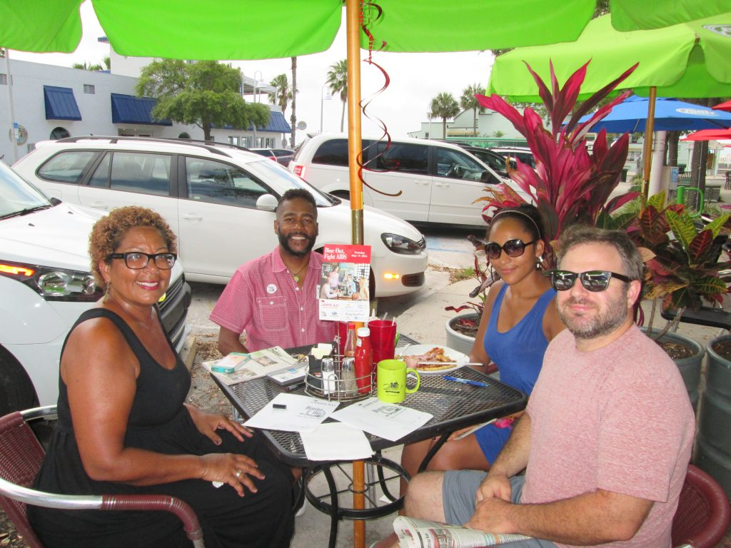 Four people sitting at an outdoor restaurant table smiling at the camera.