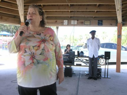 Mary Phillips of St. Petersburg sings at the karaoke at Gulfport's Pavilion 6 on Monday, April 4 while DJ Bubbling Butch, aka William McGee, a former lead singer for the funky soul band Tower of Power, stands in the background.