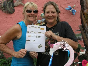 Jamie McCary, left, and Kim Schnitker, holding the ransom note, pose with Pinky in their back yard in Gulfport.