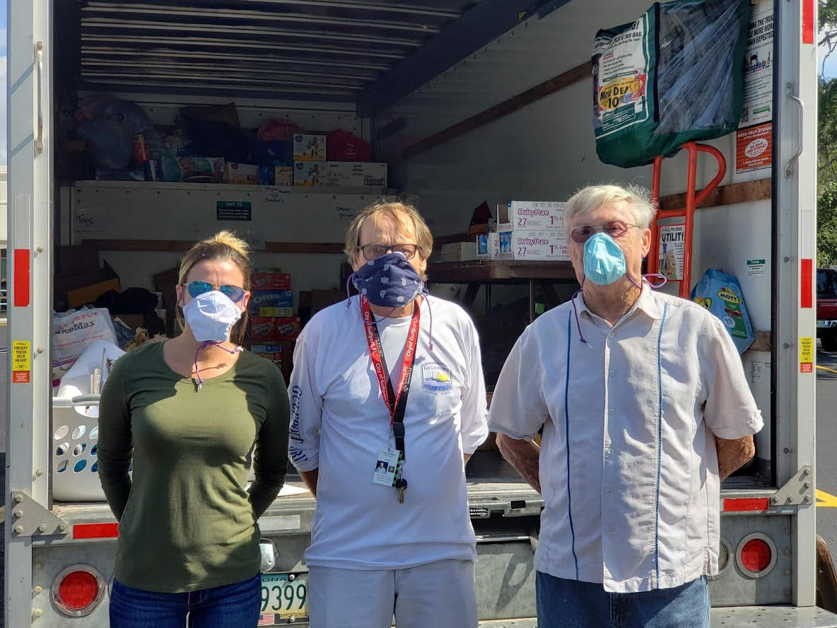 Two volunteers stand with City of Gulfport Mayor Emeritus, Michael Yakes, right, as they teamed with the Gulfport Police Department, Pinellas County Schools & Gulfport Elementary.