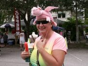 "Chris Gasco of Madeira Beach demonstrates how the wings flap on her ""flying pig"" hat as she enjoys a strawberry daiquiri frozen popsicle. ""It's quite tasty,"" she said. ""They're four ounces with an ounce of liquor in every one."""