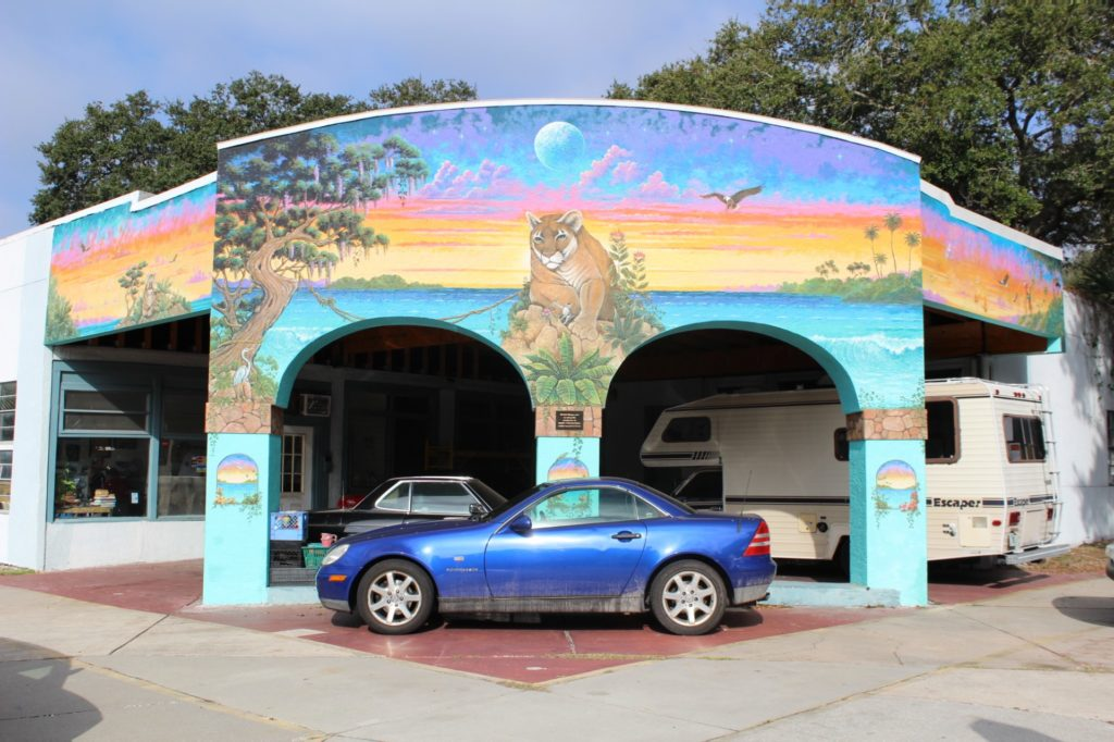 A photo of the front of a building double archway painted with a colorful mural featuring a panther, with a blue car parked in front.