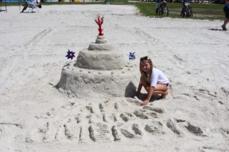 Lilian Babb poses by her sculpture at the family sand sculpture contest on the beach behind Gulfport Recreation Center.