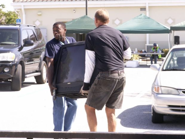 """Cory Lewis carries a television Saturday toward his car, where his wife and three of their five children await, with the help of Junk in the Trunk volunteer Wolfgang Deininger. """"I can't afford to buy one for the kids right now,"""" Lewis said. """"Hopefully, it works."""""""
