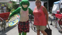 "Diane Gannon of Fort Myers poses with a large gecko that was greeting visitors during Saturday's GeckoFest. Gannon lived in Gulfport about 25 years ago. ""I try to come back every year for the festival,"" she said. ""I love the town now. I'd like to move back here, but it costs too much."""