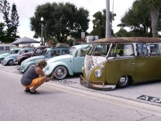 Low rider: A passerby photographs several VWs lined up on 9th Avenue in Pass-A-Grille during the seventh annual VW Beach Bash on Saturday, October 3.