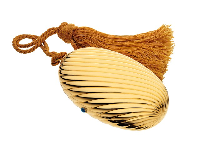 """""""Melone"""" evening bag in gold with sapphire, 1972. The polished and fluted oval case with cabochon sapphire thumbpiece, opening to reveal a fitted mirror, suspended on a golden colour silk cord terminating with a tassel. The interior is fitted with an oval mirror. With a golden coloured silk cord and tassel. Marks: on the rim (interior): """"BVLGARI"""" stamped; lozenge with """"750""""."""