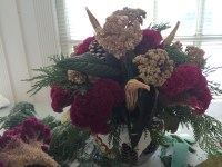 Finished arrangement in cache pot with okra pods and cockscomb