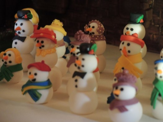 A gathering of snow men outside of the mammoth chocolate gingerbread house