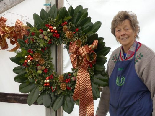 Miriam, the chief wreath maker, stand proudly next to a special ordered wreath