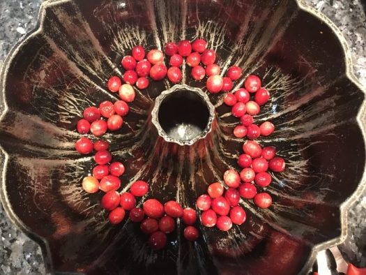 Place fresh cranberries in the bottom of a bundt pan