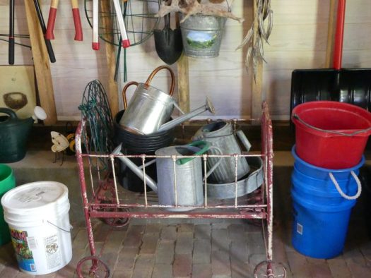 An old crib stores watering cans