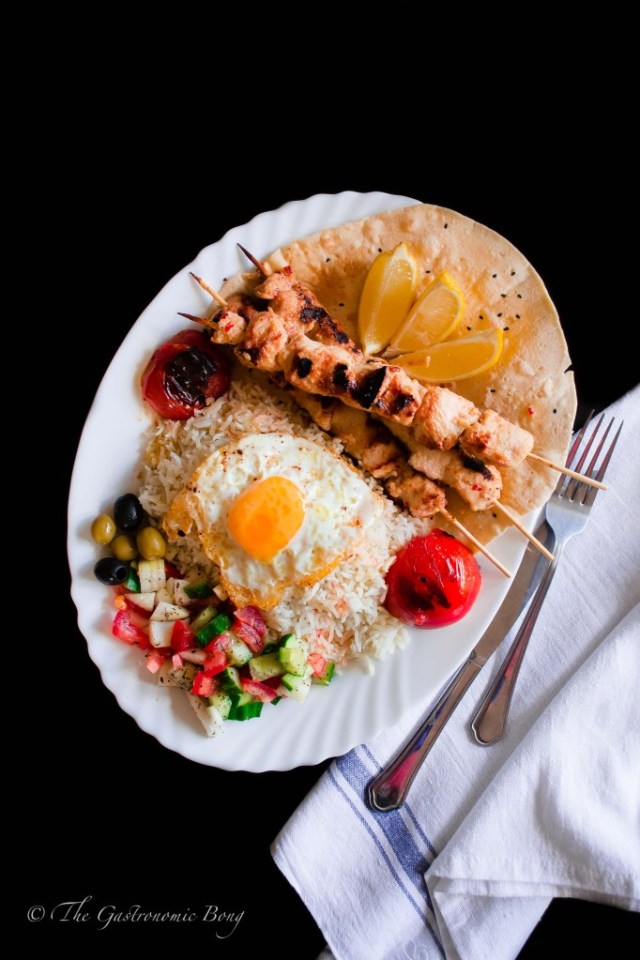 Persian Joojeh {Chicken} Kebab on a bed of Chelo, Fried Egg and Salad Shiraza
