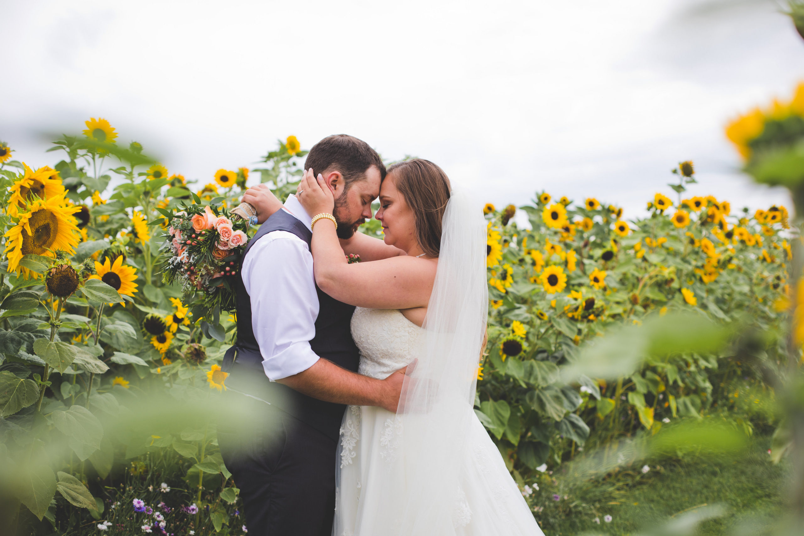 Bright yellow sunflowers surround a bride and groom as they stand in the garden. The Gathered - Southern Alberta