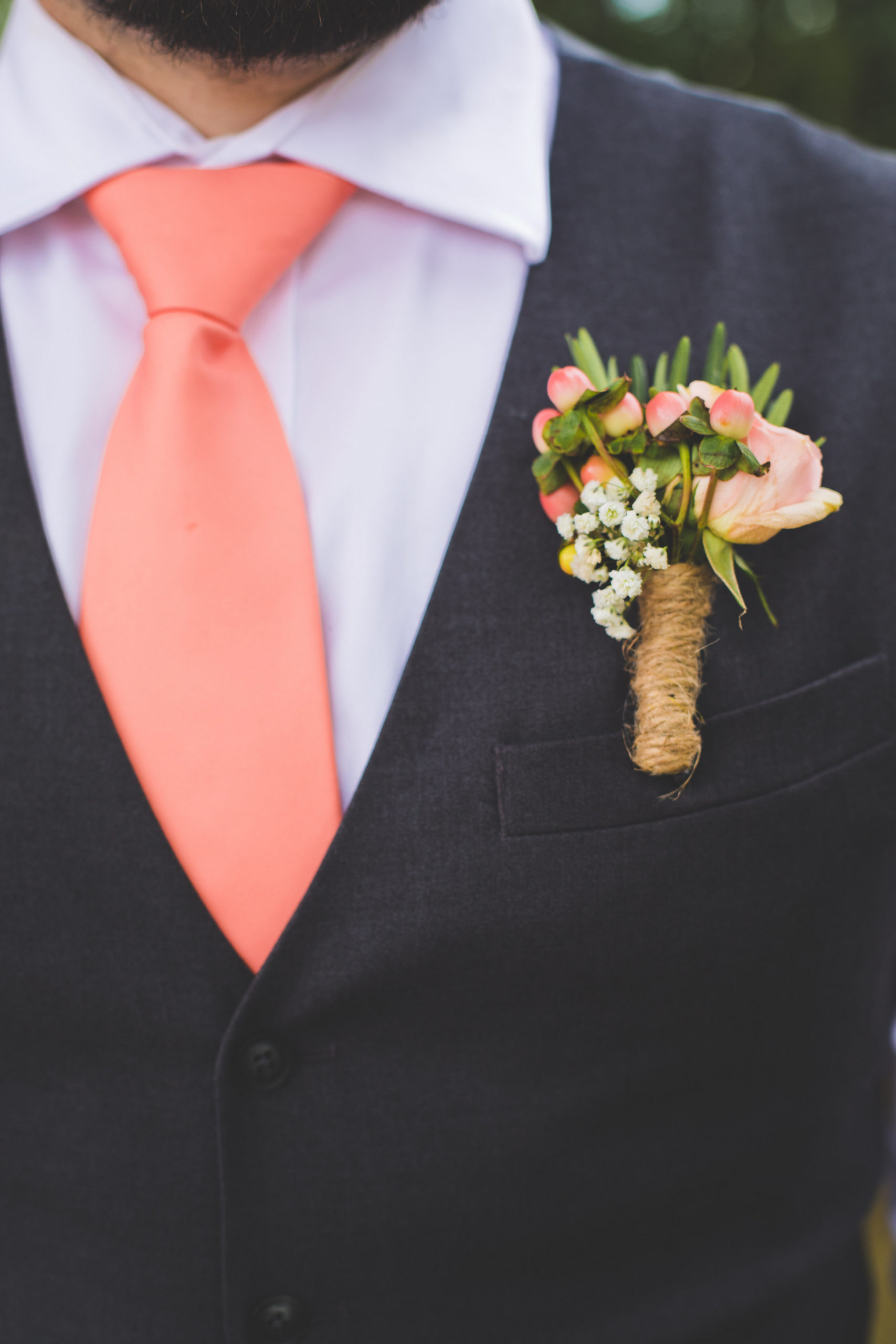 Coral and Peach tie accents the navy blue wedding vest. A pink- coral- peach boutonnière accompanies the coral tie.