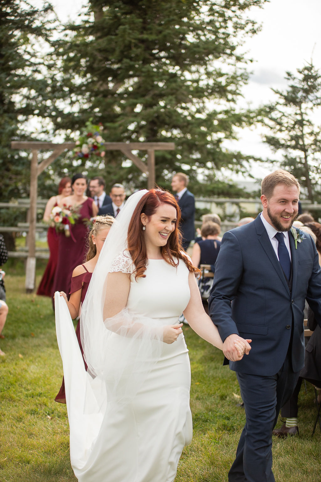 walking down the aisle just married surrounded by friends and family at their outdoor wedding ceremony at the Gathered. www.thegathered.ca