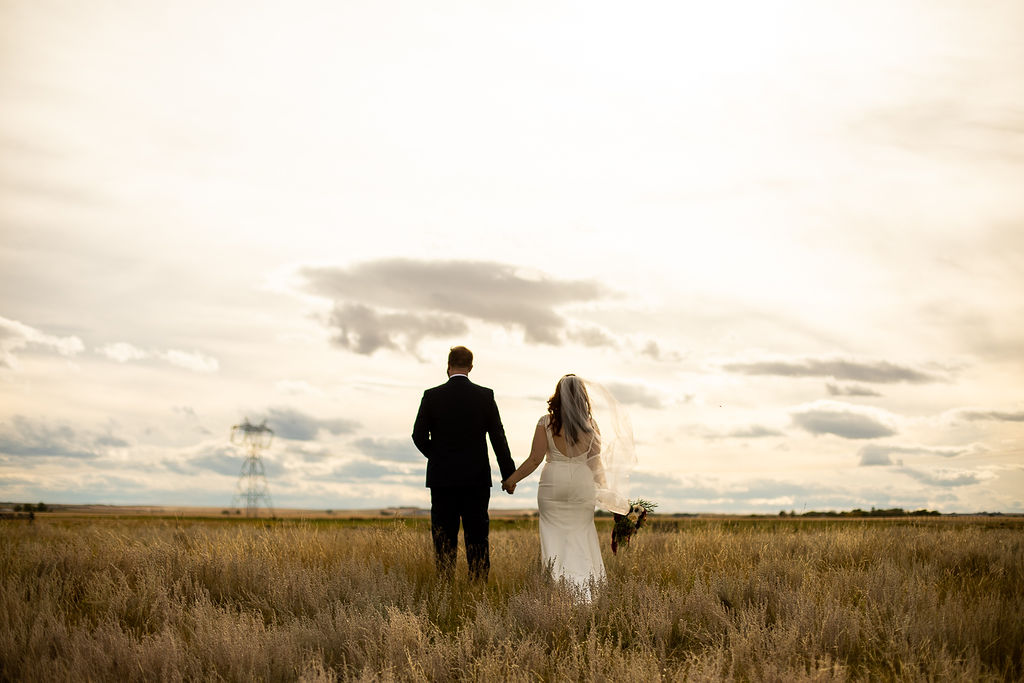 golden prairie fields and overcast sky make the perfect backdrop for this wedding couple at their prairie outdoor wedding. www.thegathered.ca