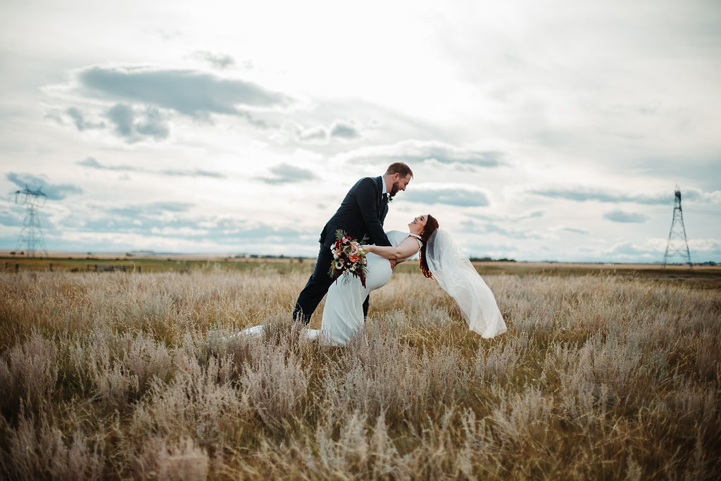 a groom dips his bride in a wild prairie field setting with an overcast sky in the backdrop. www.thegathered.ca