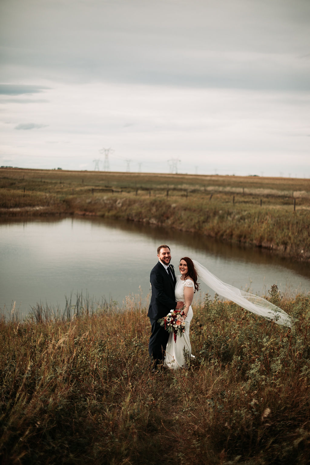 prairie fields surround a pond of water, a couple stands beside the water while the brides veil blows in the wind. www.thegathered.ca