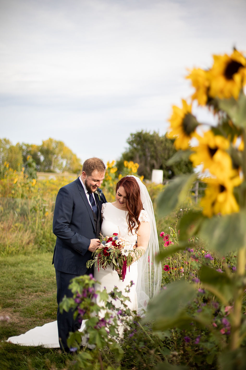 bride and groom stand beside wild flower garden at their outdoor wedding in Calgary, Alberta. www.thegathered.ca