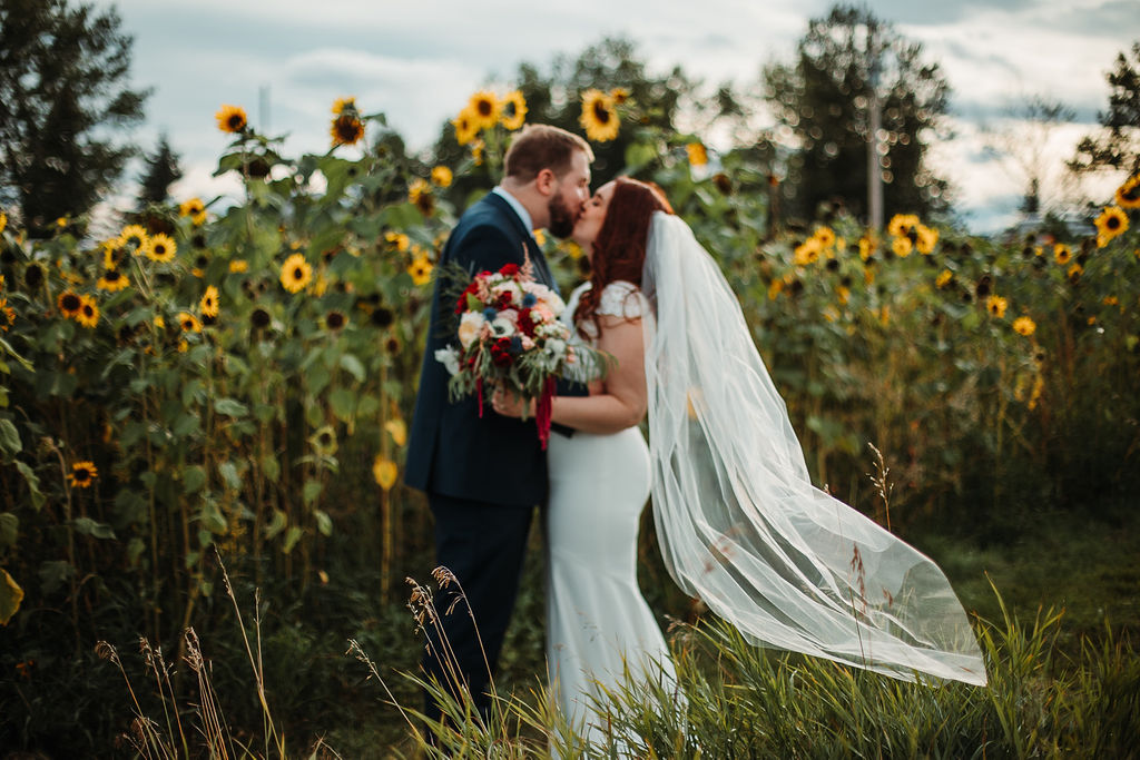 a blurry shot of a couple kissing beside a row of sunflowers