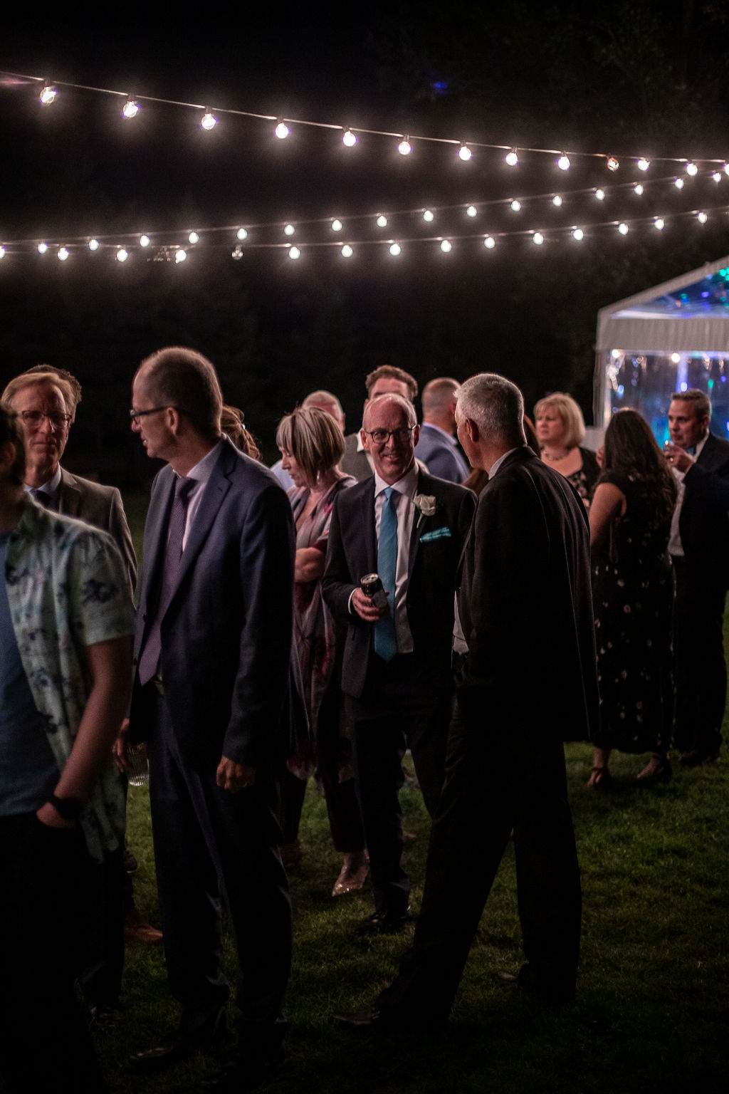 wedding guests stand in the dessert line while globe lights are strung overtop