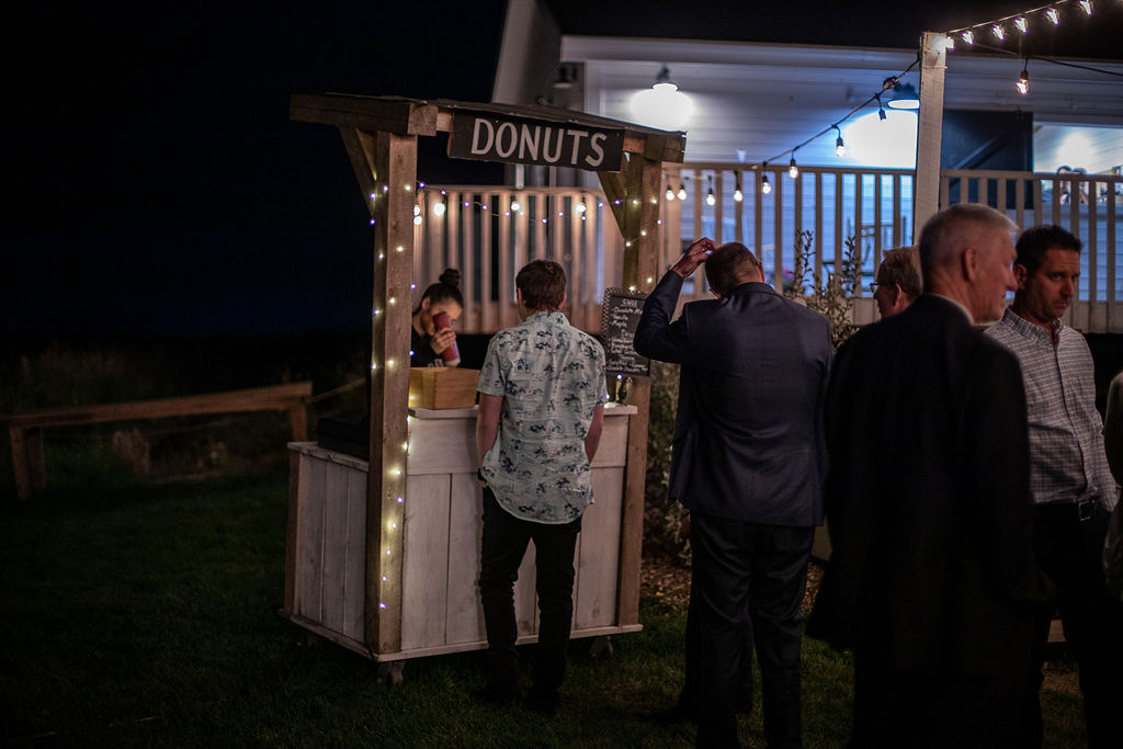 a wooden donut stand offers donuts at this outdoor wedding venue in Calgary, Alberta.