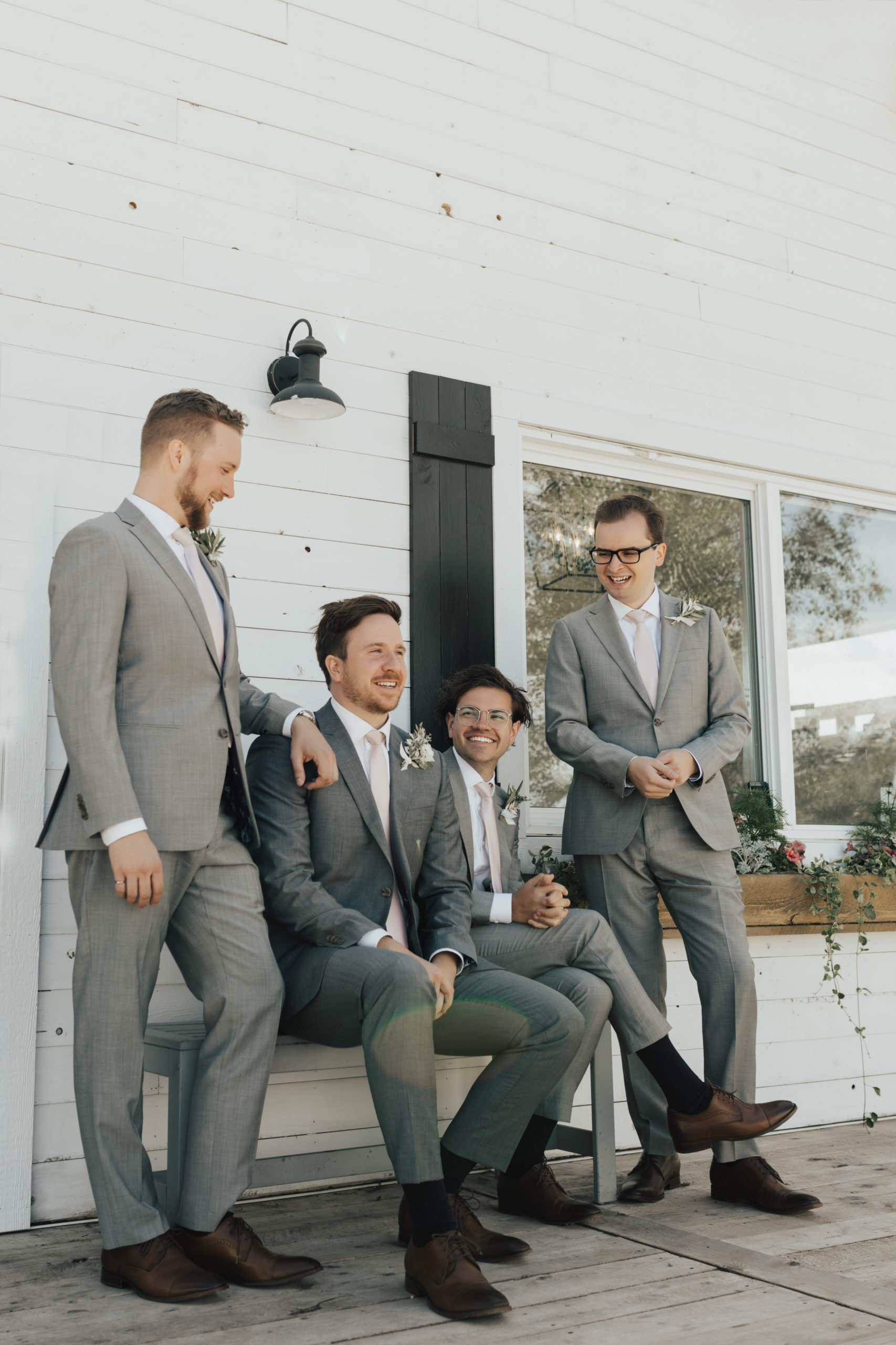 groomsmen with grey suits and pink ties sit outside a white cottage with black shutters