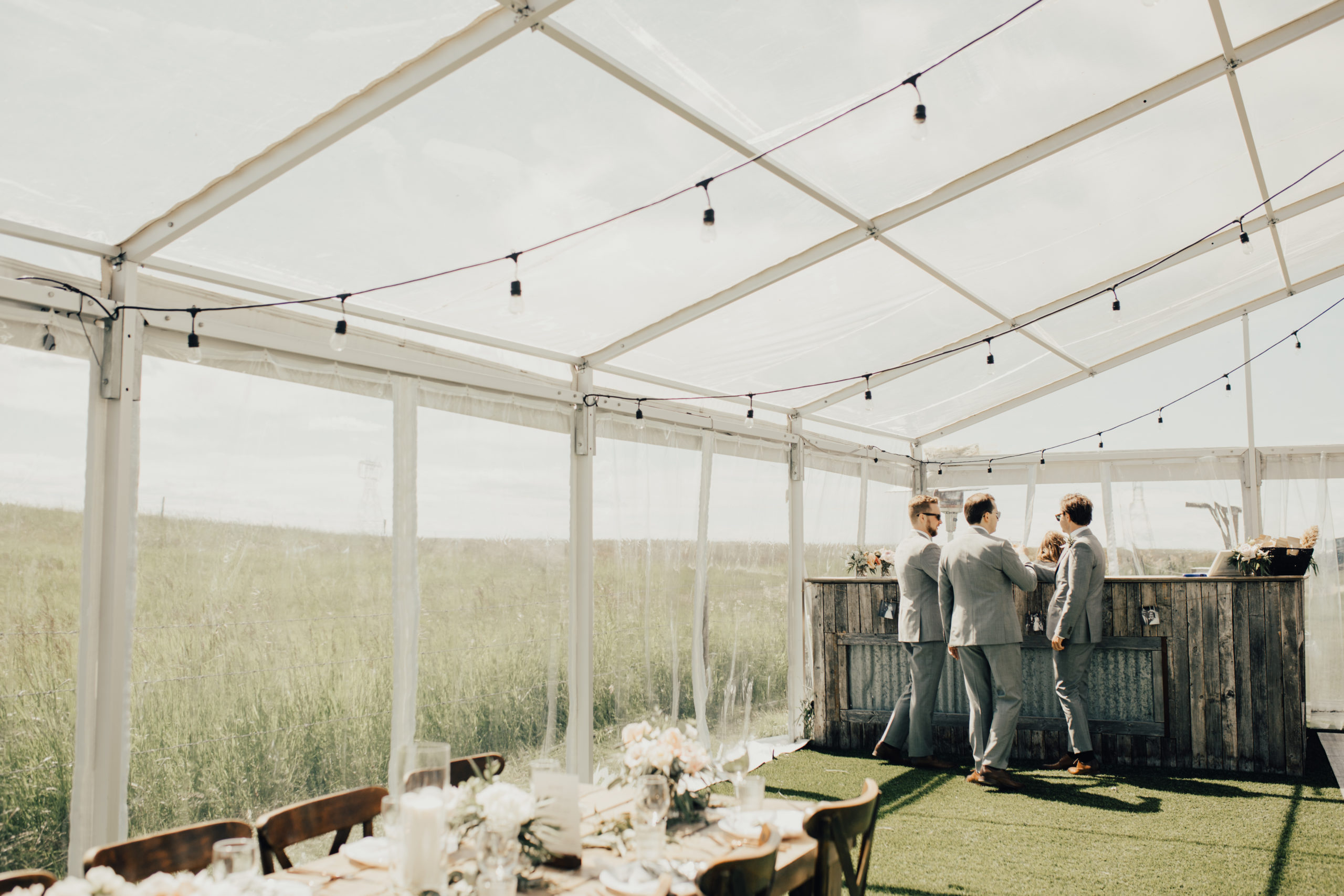 groomsmen stand at a wood bar in a clear tent with black globe lights
