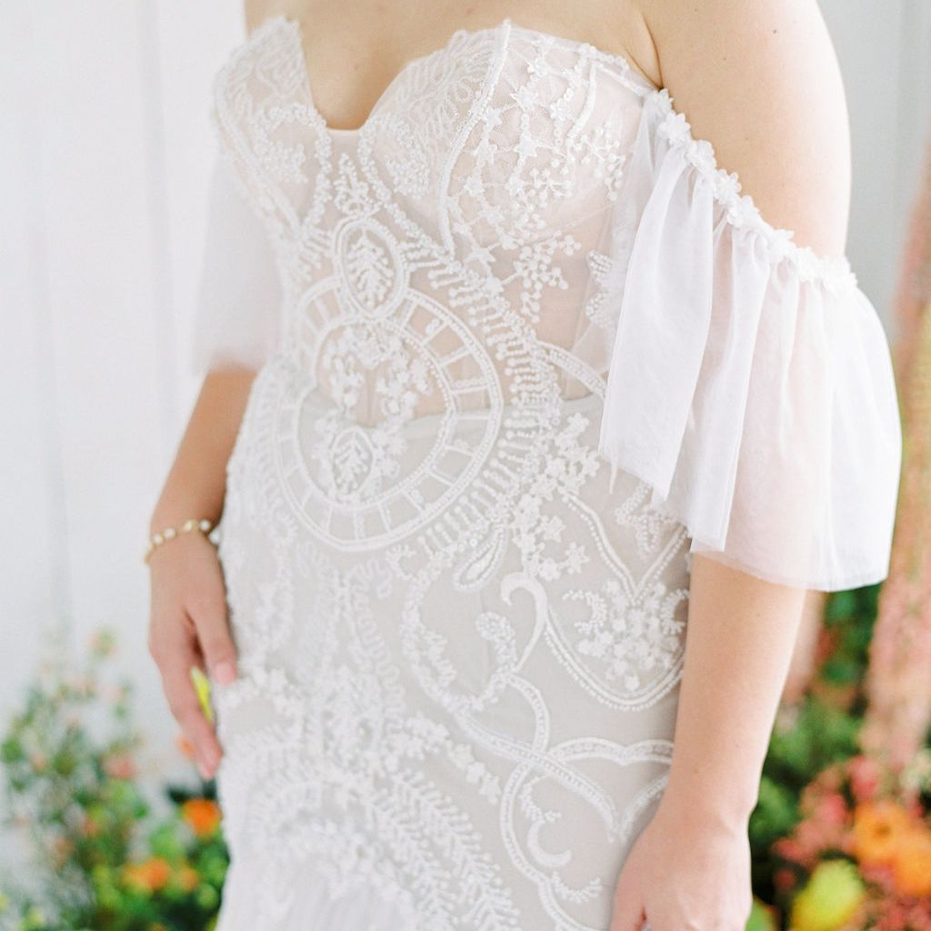 lacy off the shoulder white wedding dress with antique inspiration perfect for a spring styled wedding