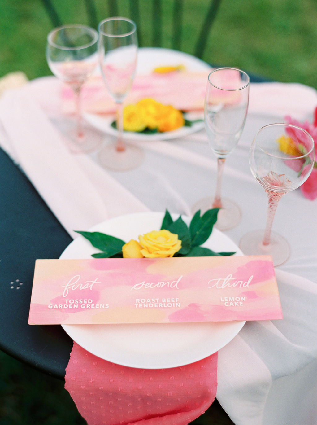 pink table arrangements with orange and pink seating cards and pink wine goblets