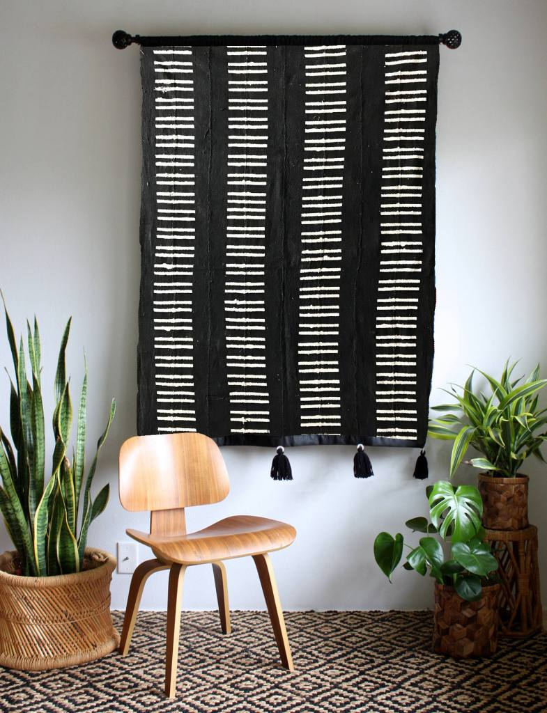 hanging black rugs behind wooden chair - wall art idea