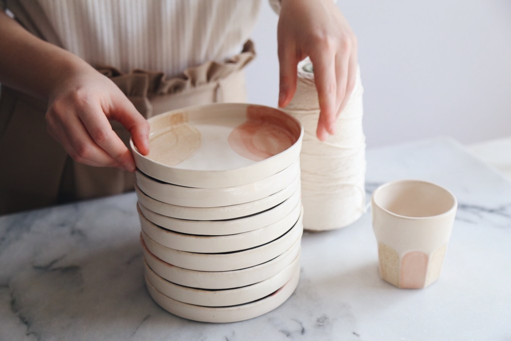 Ceramic Studio Maitoinen - plates in pile and hands