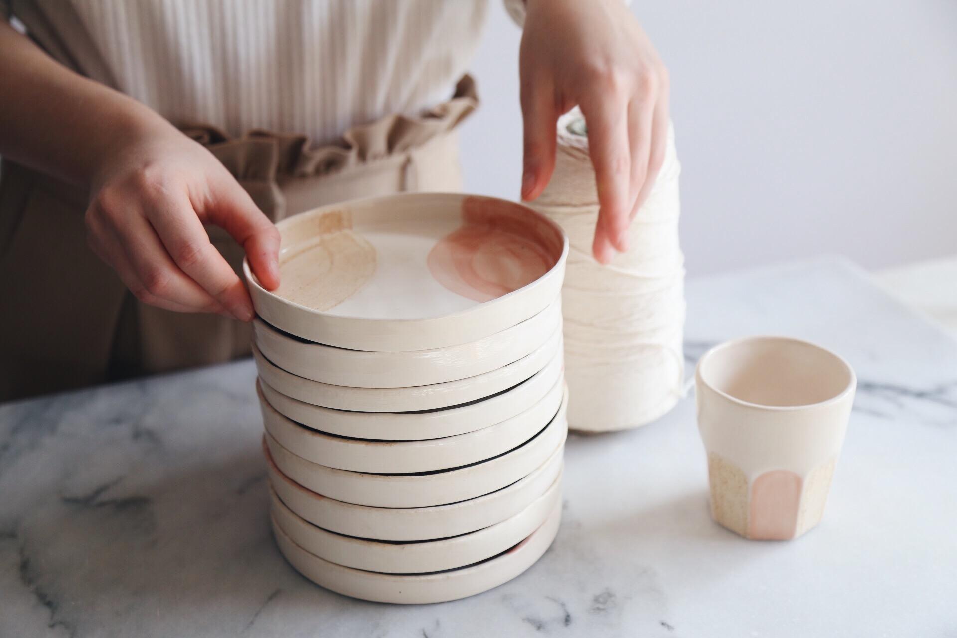 Ceramic Studio Maitoinen - plates in pile and hands