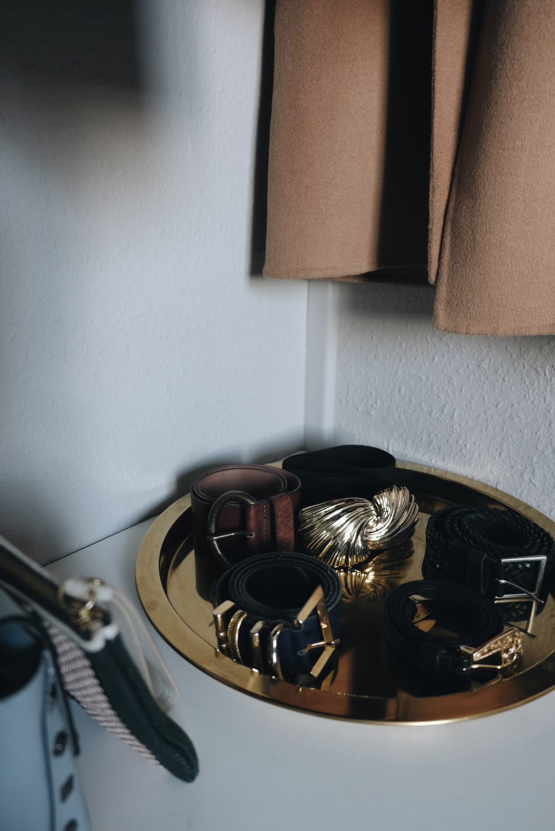 small space closet organization: belts in a brass tray