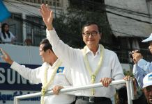 Sam Rainsy and Kem Sokha wave to protesters