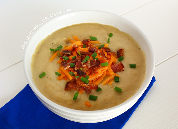 Potato soup in a bowl garnished with bacon, cheese and chives.