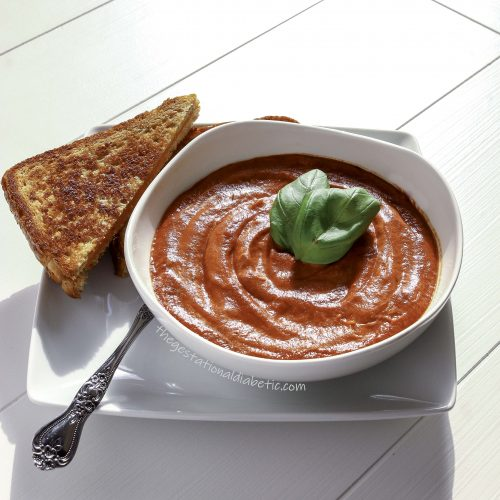 Tomato soup in a bowl with basil leaves and a spoon and grilled cheese