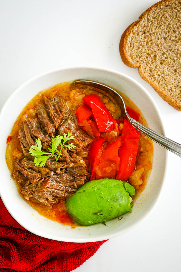 overhead look of bowl with ropa vieja, avocado and red bell pepper with 1 slice of wheat bread