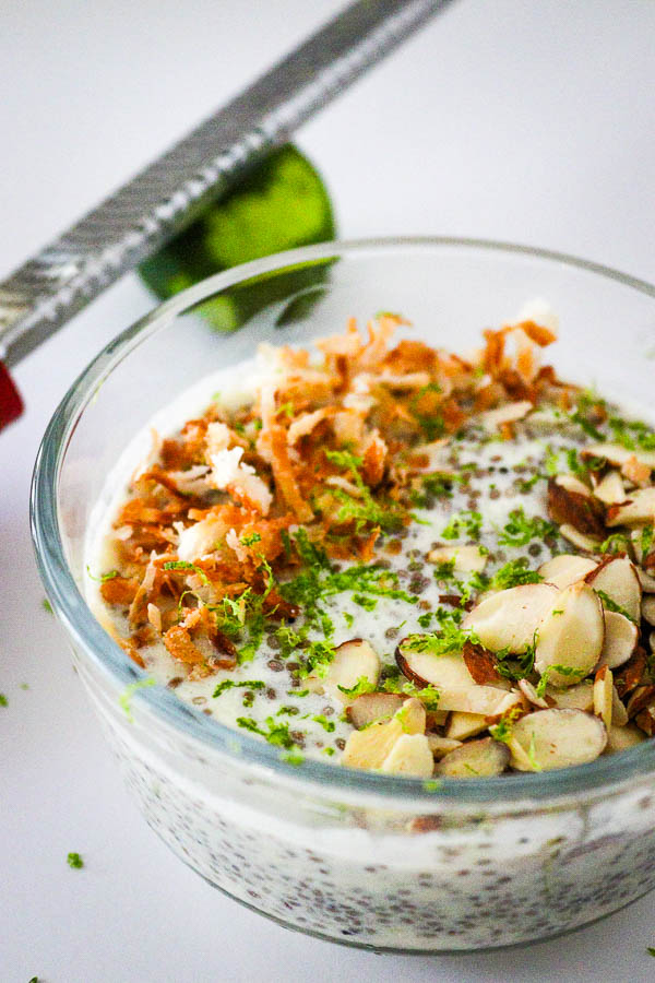Healthy Pina Colada Chia Pudding in glass bowl topped with toasted coconut, almonds and lime zest