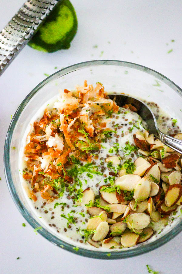 Healthy Pina Colada Chia Pudding in glass bowl topped with toasted coconut, almonds and lime zest overhead look 2