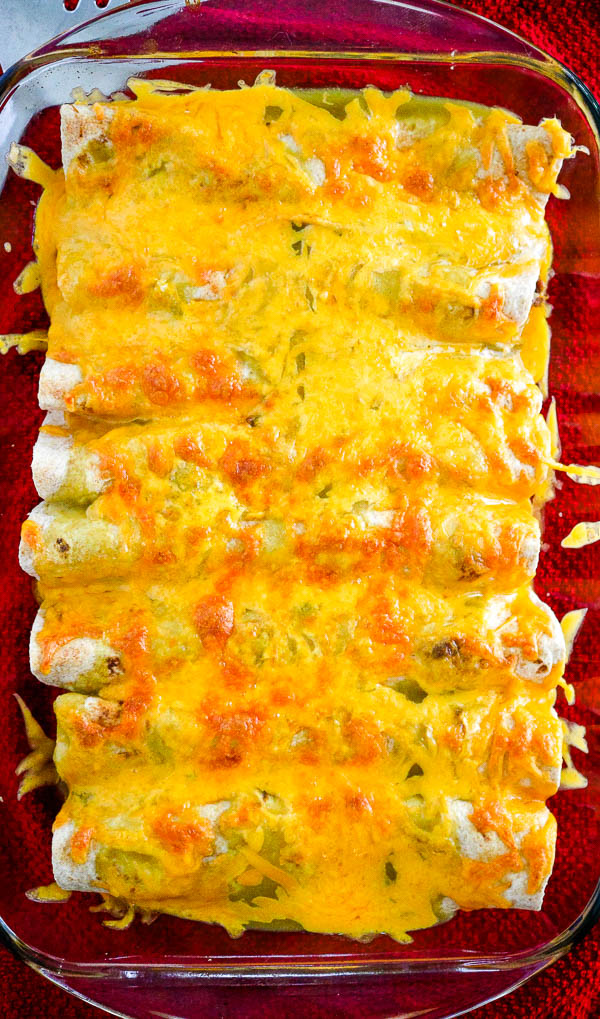 overhead look of burritos topped with melted cheese in a casserole dish