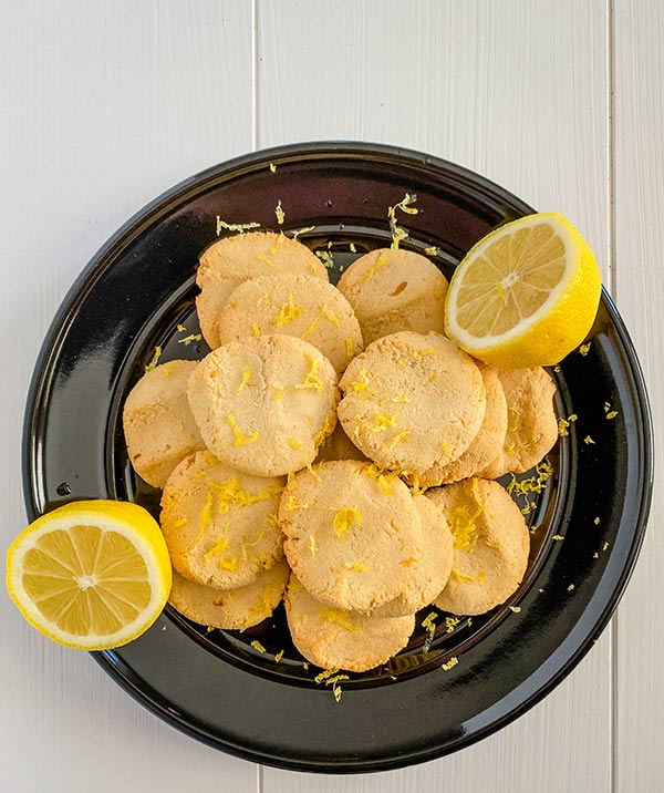 overhead view of soft lemon cookies on a black plate with a lemon halved and zested over the cookies