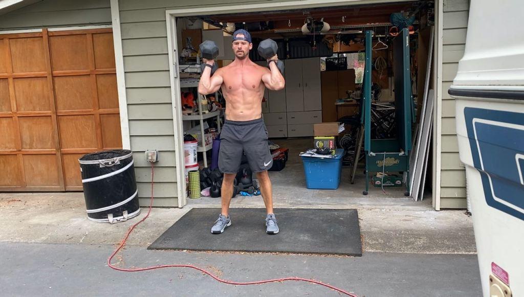 Joe doing dumbbell cleans outside of garage
