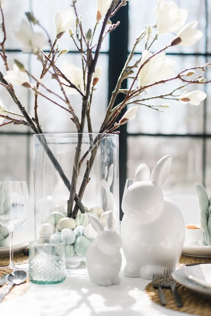 White ceramic bunnies and magnolia stems buried in easter eggs add Easter style to a simple neutral tablescape