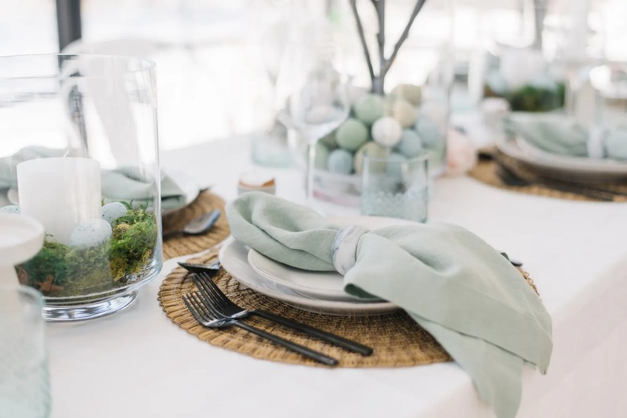 An Easter table setting with linens, moss centerpieces and faux speckled eggs