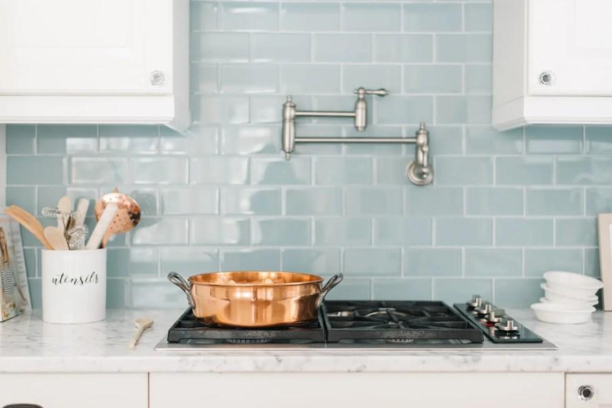 Custom kitchen with blue backsplash tile above the gas stovetop